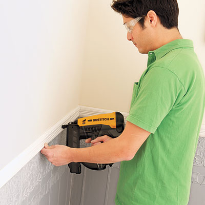 installing the chair rail molding to cap off the newly-installed Lincrusta wainscot panels with a pneumatic brad nailer