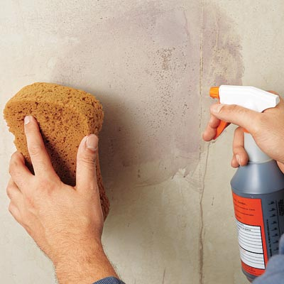 checking for residual adhesive by spraying the wall with povidone iodine and water and wiping with a sponge