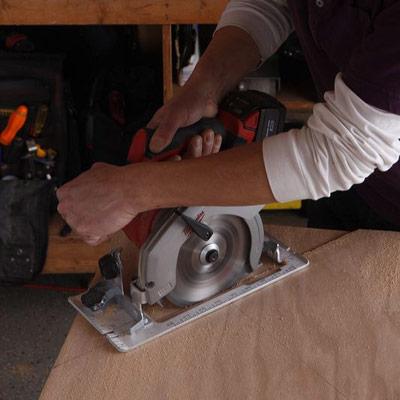 man using circular saw to make poker table