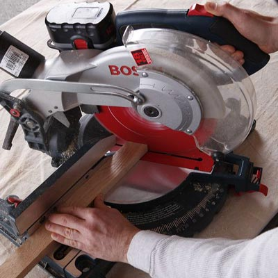 man using miter saw to construct poker table