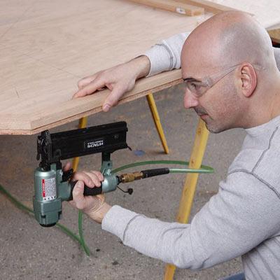 man using nail gun to construct poker table
