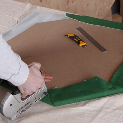 two men attaching felt to poker table