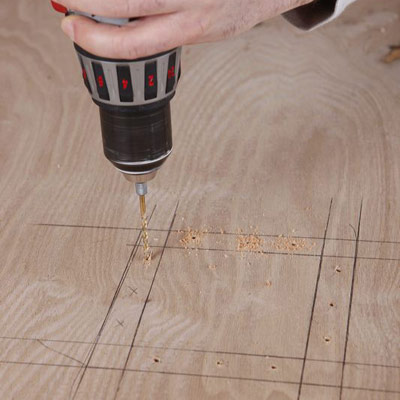 man drilling pilot holes on poker table