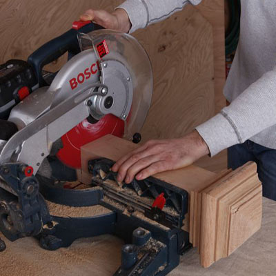 man using miter saw to cut poker table stand