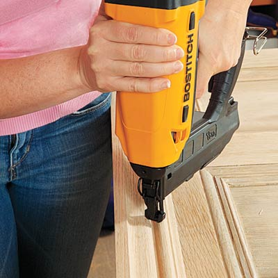 securing crown to the repurposed door to make the top of the headboard with a brad nailer
