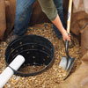 shoveling rounded stones into the dry well hole