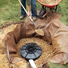 filling up the hole around the dry-well with rounded stones