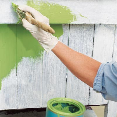 applying a base coat of green paint to a kitchen island before applying faux crackle