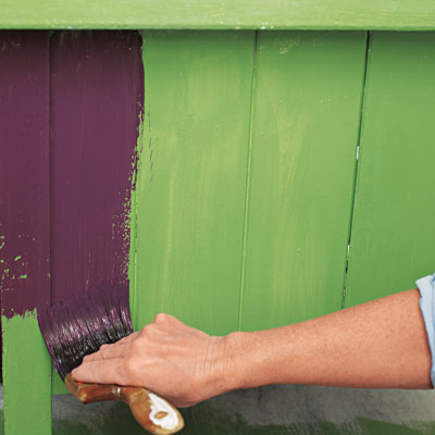 applying a top coat of purple paint over faux crackle for a kitchen island
