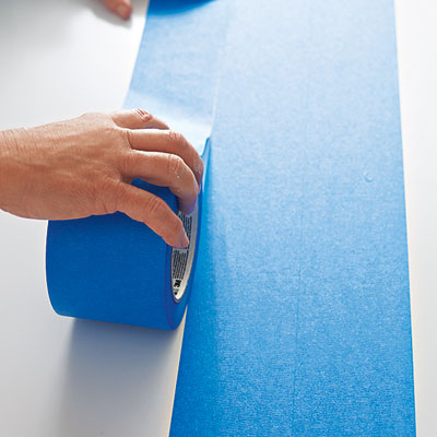 laying the third row of painter's tape on a table surface