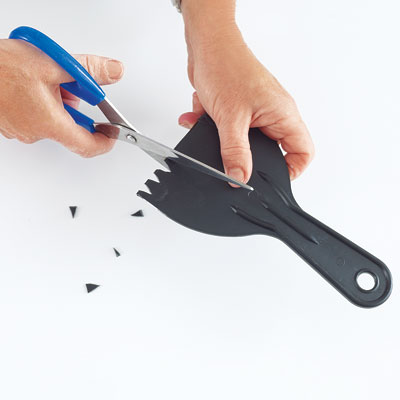 cutting notches in a plastic putty knife for the combing tool