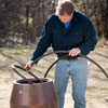 Roger Cook adds tubing to a rain barrel