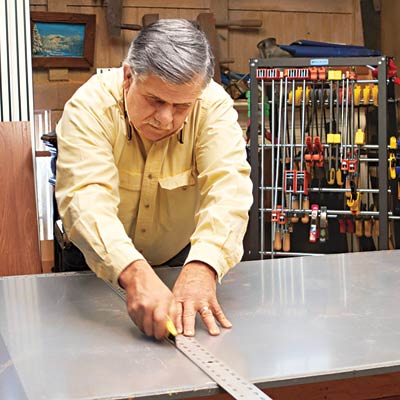 Tom Silva trims the acrylic top with a straightedge and utility knife