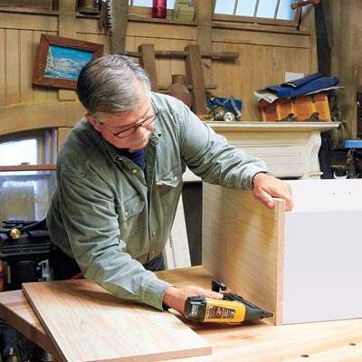 Tom Silva attaches the base to the bookcase