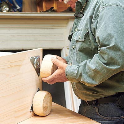 Tom Silva adds the feet to the bottom corners of the bookcase