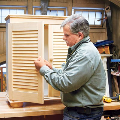 Tom Silva attaches the knobs to the shutter doors