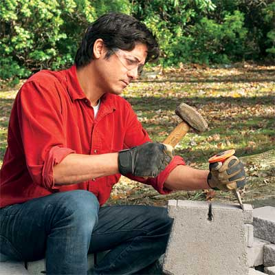 person fitting blocks to build a stone planter