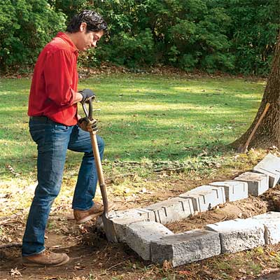 person using stones to make a rough outline to build a stone planter
