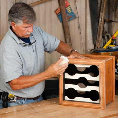 Tom Silva sands the completed wine rack