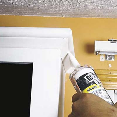 applying caulk to seams in primed cabinets