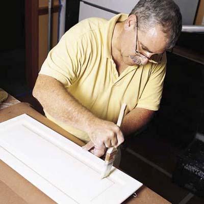 John Dee applying the finish coat to a cabinet door