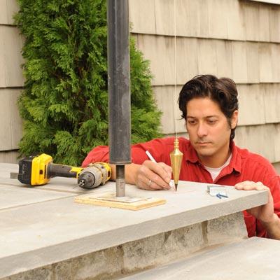 person marking porch post location