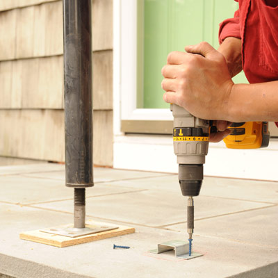 person drilling brackets into porch