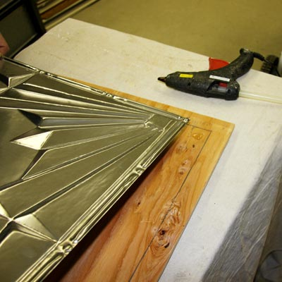 applying the tin-tile to the plywood frame with hot-glue