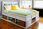 a finished storage bed with beadboard sides above open shelves. a green throw covers the bed with a stack of yellow and patterned pillows leasing against a white beadboard headboard. The bed is in bright room with bay windows and hardwood floors