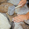 lining up and hammering in stones for building a fieldstone wall 