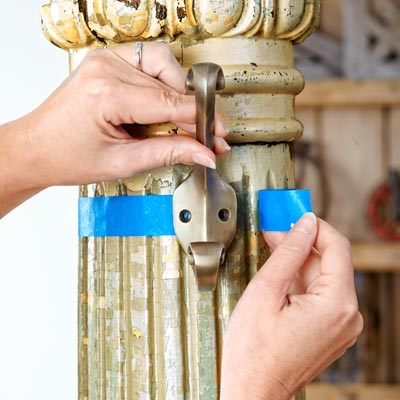 painter's tape marks the diameter of an antique column for hanging hooks