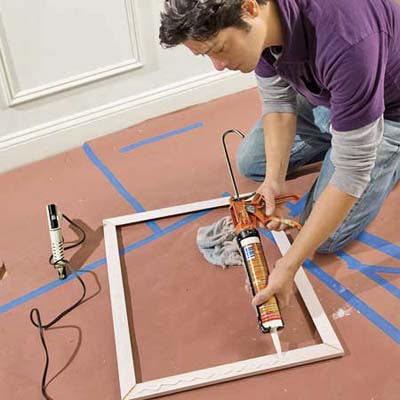 Using a caulk gun, apply panel adhesive to the four sides of the frame