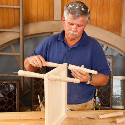 Tom Silva attaching table legs to the middle tray