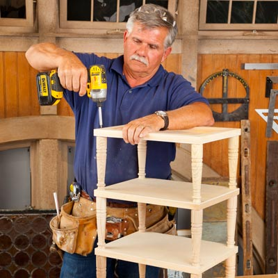 Tom Silva attaching the top tier to a 3-tiered side table