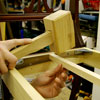 tapping a cross-piece into place across the center of the bench frame with a wooden mallet