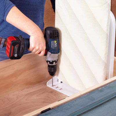 securing an ironing board to the inside of the cabinet