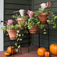 halloween planters with fake zombie hands and vintage garden tools on porch