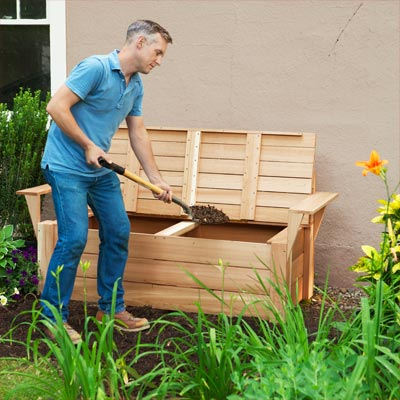 person turning compost in their compost bench