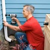 drilling a hole in the downspout to accommodate the rain barrel