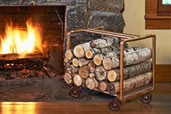 a copper-pipe log holder next to a roaring fireplace