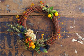 grapevine wreath made with dried flowers and fruit lying on a distressed wood table