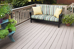 light brown, recently-refinished deck with potted plants against two of the railings, and an outdoor couch at the far end