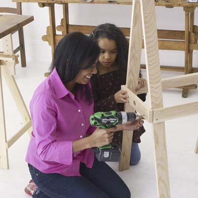 Family attaching the cross braces and brackets to build an easel