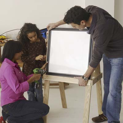 Family mounting the boards to build an easel