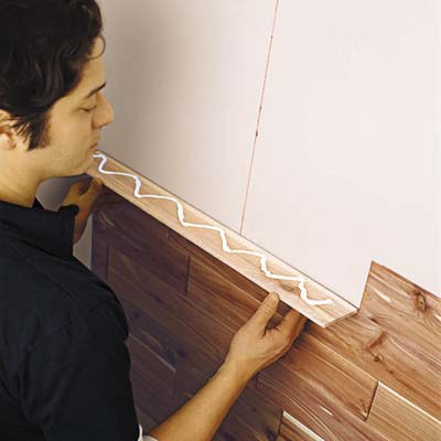Photo of man attaching glued board to the wall, interlocking with the groove of the board below it.