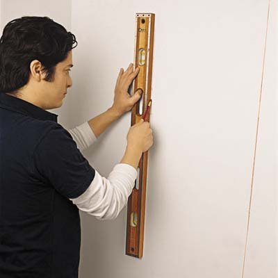 Image of person holding a level to the wall to mark the line of studs, once found with the stud finder.