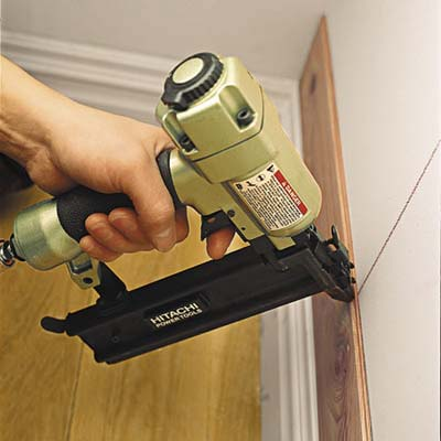 Image of a nail gun attaching cedar to the wall