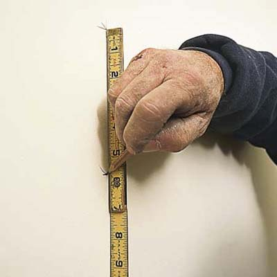 tom silva measuring with a measuring tape, and marking layout line of the wall with a pencil