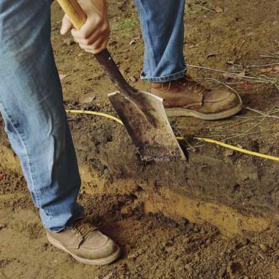 excavating soil to build a brick walkway