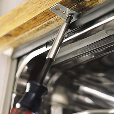 Screws are drawn in the mounting brackets to fasten dshwasher underside of the countertop